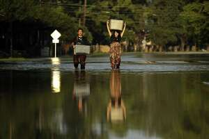FILE - In this Monday, Sept. 4, 2017 file photo, Mariko Shimmi, right, helps carry items out of the home of Ken Tani in a neighborhood still flooded from Harvey in Houston. Thousands of people were displaced by torrential rains and catastrophic flooding after Harvey slammed into Southeast Texas in late August, 2017. (AP Photo/Gregory Bull)