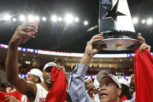 Houston head coach Kelvin Sampson holds up the American Athletic Conference championship trophy as the Cougars celebrate after beating Southern Methodist 90-79 to win at least a share of the AAC at Fertitta Center on Thursday, March 7, 2019, in Houston.