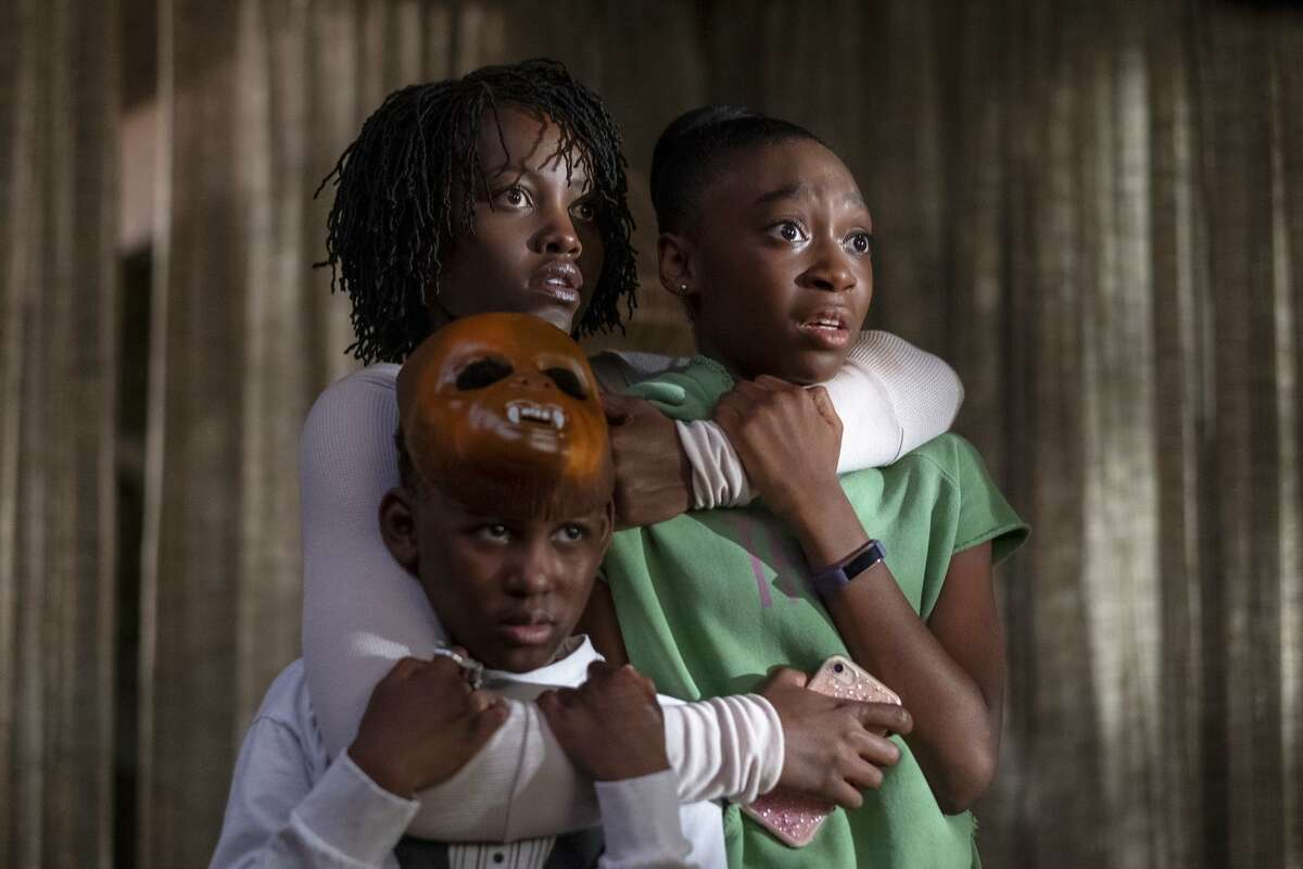 """This image released by Universal Pictures shows, from left, Evan Alex, Lupita Nyong'o and Shahadi Wright Joseph in a scene from """"Us,"""" written, produced and directed by Jordan Peele. (Claudette Barius/Universal Pictures via AP)"""