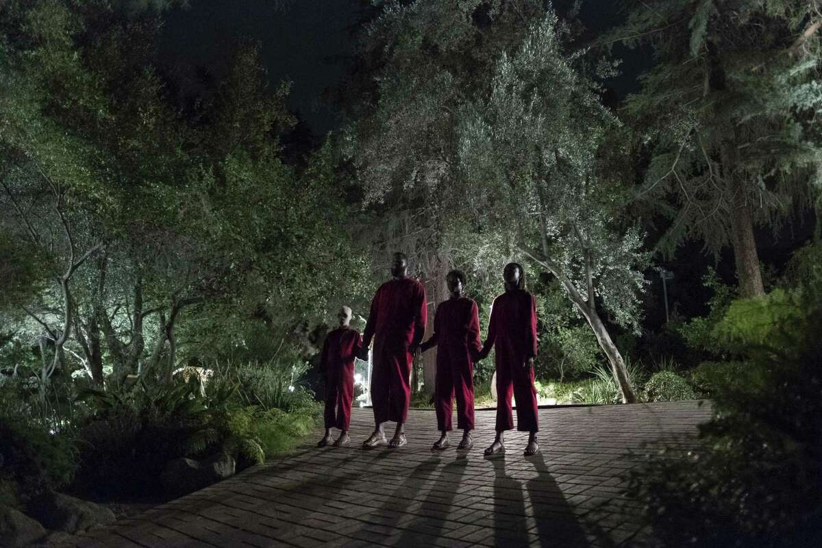"""This image released by Universal Pictures shows Evan Alex, from left, Winston Duke, Shahadi Wright Joseph and Lupita Nyong'o in a scene from """"Us,"""" written, produced and directed by Jordan Peele. (Claudette Barius/Universal Pictures via AP)"""