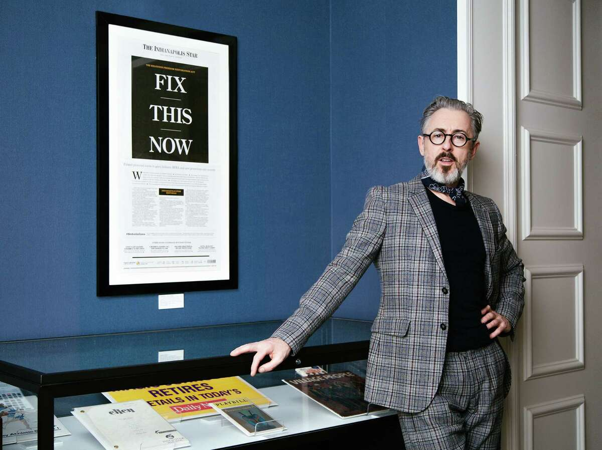 """Alan Cumming poses next to artifacts he selected for the """"Newsroom: Rise Up"""" suite at the Hamilton Hotel in Washington, D.C., on March 18."""