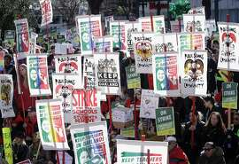 FILE - In this Thursday, Feb. 21, 2019 file photo teachers, students and supporters hold signs at Frank Ogawa Plaza in front of City Hall in Oakland, Calif. Teachers in Oakland  hit the picket lines just as West Virginia teachers went back to class this week in a display of the national teacher unrest that in many places has moved beyond pay to politics, tackling issues like charter schools and vouchers. (AP Photo/Jeff Chiu,File)