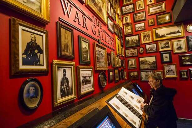 Barbara Martin-Smith flips through a gallery of photos at the Abraham Lincoln Presidential Library and Museum in Springfield, Ill.