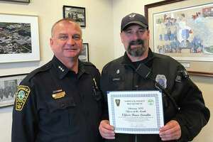 "Officer Bruce Lovallo accepts the ""Officer of the Month"" award from Norwalk Police Chief Thomas Kulhawik."