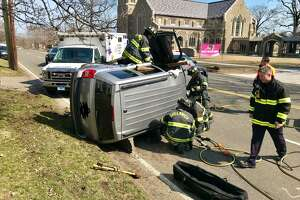 Greenwich firefighters work to free the driver from a rollover crash on East Putnam Avenue on Wednesday afternoon.