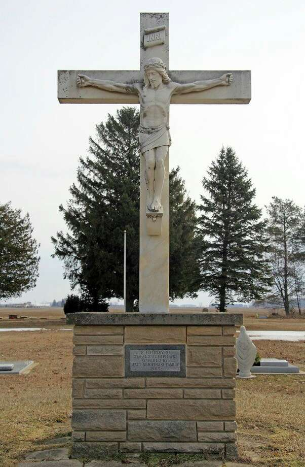 The white marble statue depicting a crucified Jesus, as it stands at the Saint Joseph Cemetery in Rapson today. (Seth Stapleton/Huron Daily Tribune)