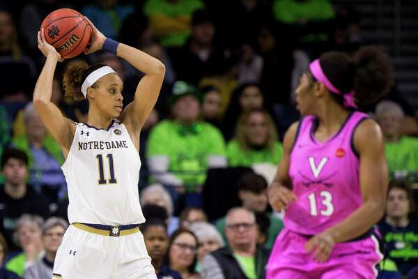 Notre Dame's Brianna Turner (11) looks to pass around Virginia's Jocelyn Willoughby (13) during an NCAA college basketball game Sunday, March 3, 2019, in South Bend, Ind. Notre Dame won 103-66. (AP Photo/Robert Franklin)