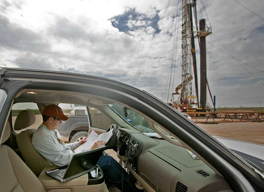 Joe Pfeil, an engineer with Devon Energy, on an active pumping rig located on Highway 385 south of Odessa, photographed Tuesday, Sept. 24, 2014.