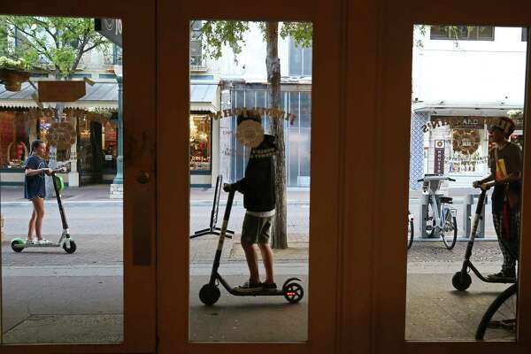 """Scooter riders use the sidewalk along Houston Street in downtown San Antonio, Wednesday, March 13, 2019. The scooter rental comes with an 18,404 agreement that straightjackets the customer. The riders had agreed to never sue Lime, take responsibility for all accidents and damage, accept binding arbitration in lieu of any jury trial, limit Lime's liability in any event to only $100, waive all participation in class action lawsuits and, among a maze of other promises, affirm that they've not had any drug or alcohol """"incidents"""" in the past seven years. They even agreed that Lime has never implied that its """"equipment will be in good repair."""" Virtually every scooter company requires consent to a similar agreement before letting anyone activate one of the city's now-ubiquitous dockless vehicles."""