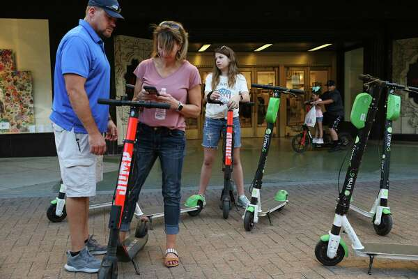 Clover Alexander, of Chico, Texas, uses her smartphone to rent scooters for her husband, Kevin Alexander and their daughter, Bethany, downtown.