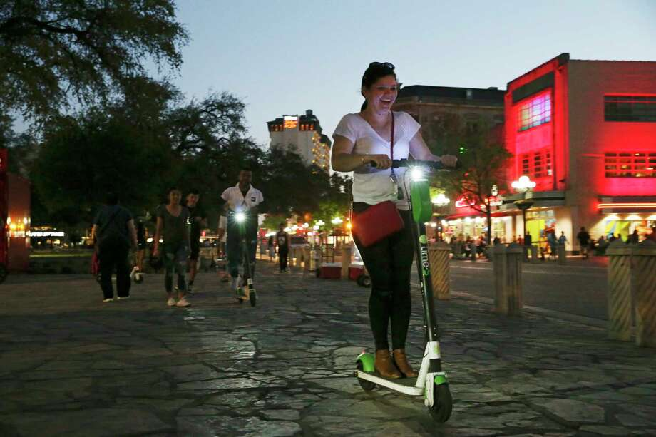 Lime scooter riders use the sidewalk of Alamo Plaza. The rental requires consent to an 18,404-word agreement, longer but similar to virtually every scooter company. Photo: Jerry Lara, Staff Photographer / © 2019 San Antonio Express-News