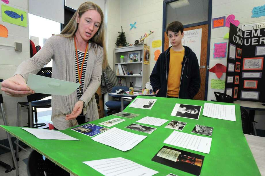 Laura Czegledi works with her Gifted and Talented students including 7th grader Vincent Mola on his National History Day project, Radium Girls: Precision Painting Turned Tragic, Wednesday, March 20, 2019, at Roton in Norwalk, Conn. National History Day is program for students in grades 6-through-12 that encourages exploration of local, state, national and world history. Students from across the district are gearing up to participate in the National History Day Regional Competition in Fairfield on April 6. Students conducted research on a historical topic and created a final project to demonstrate their work. Photo: Erik Trautmann / Hearst Connecticut Media / Norwalk Hour