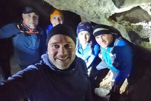 Brit Lee-Stuart Evans, forefront, is retracing the steps of Connecticut's legend The Leatherman, hiking for a week along a 41-town loop which began in New York on the evening of March 13. Here, Evans is shown with members of the Leatherman Harriers running group in one of The Leatherman's caves in Pound Ridge, New York.