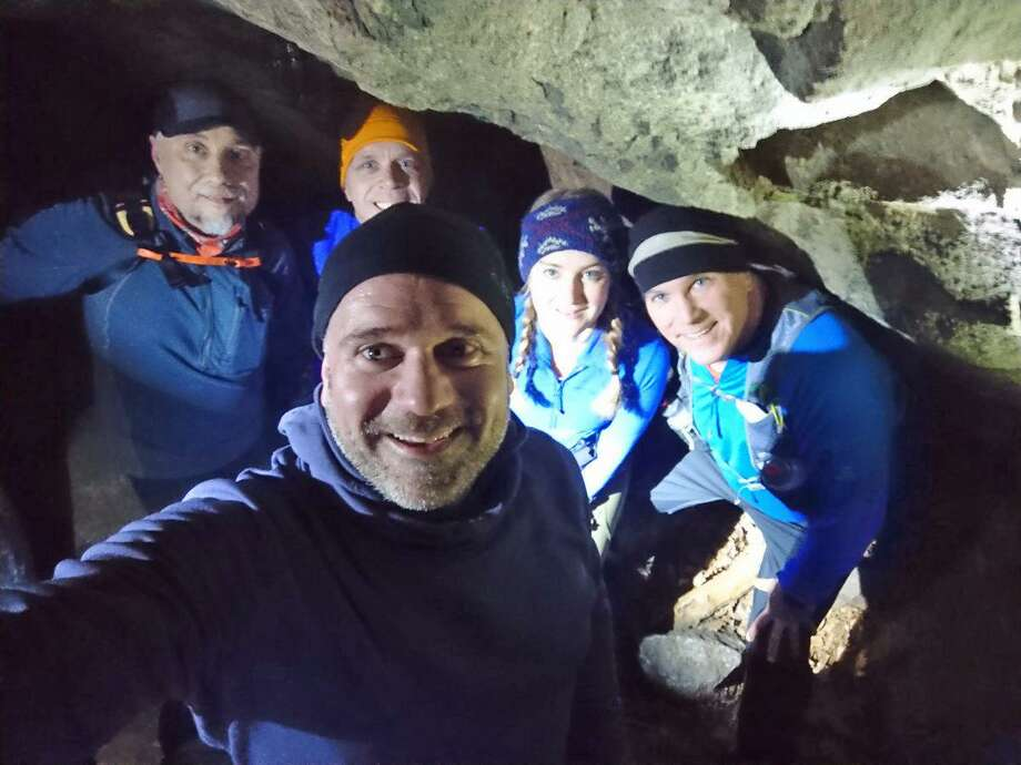 Brit Lee-Stuart Evans, forefront, is retracing the steps of Connecticut's legend The Leatherman, hiking for a week along a 41-town loop which began in New York on the evening of March 13. Here, Evans is shown with members of the Leatherman Harriers running group in one of The Leatherman's caves in Pound Ridge, New York. Photo: Contributed Photo