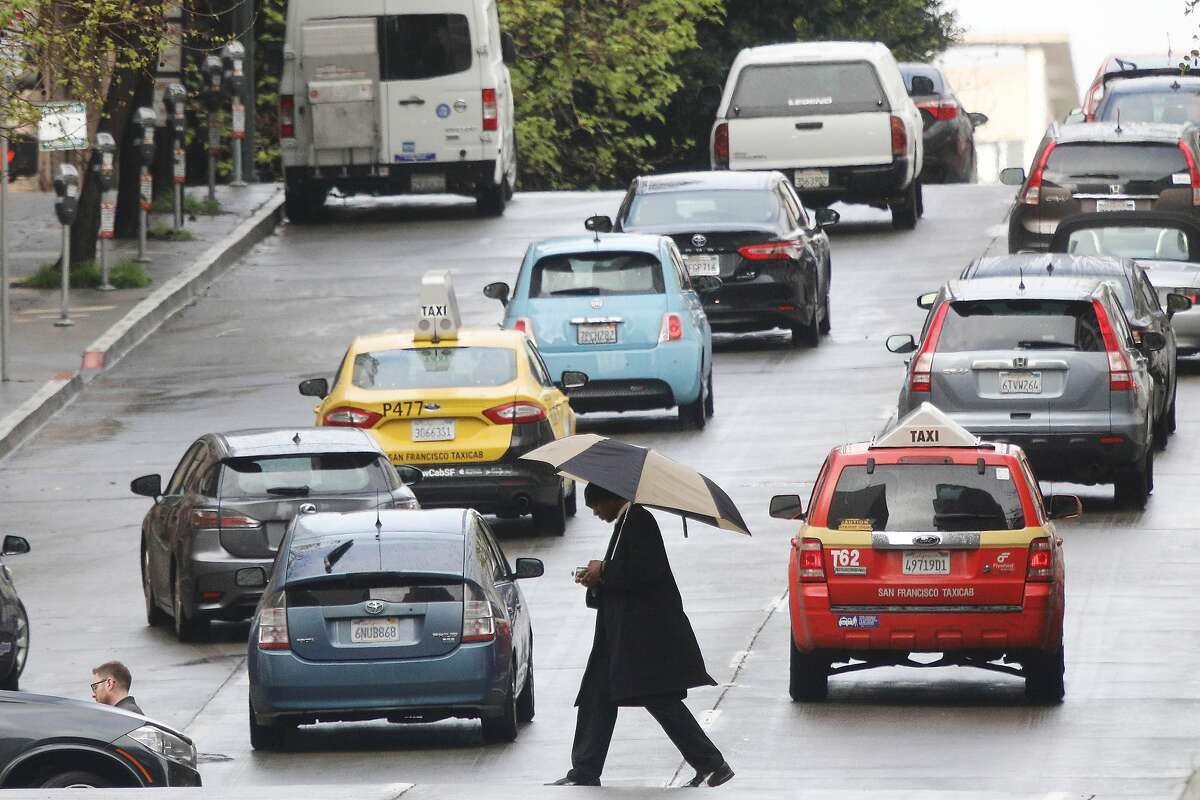 A pedestrian walks between cars while crossing Pine Street at Grant Avenue under an umbrella on Wednesday, March 20, 2019 in San Francisco, Calif.