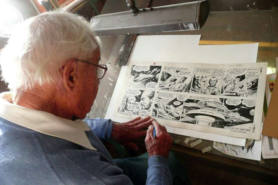 Greenwich resident Bob Fujitani points out a Flash Gordon strip he illustrated. âÄúImagination was a must in (the cartooning) business,âÄù he says. âÄúI was just making this stuff up.âÄù Photo: Picasa / Anne W. Semmes / Greenwich Citizen