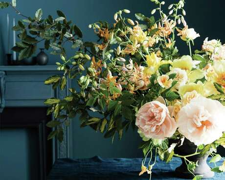 """Ariella Chezar's Spring Iris arrangement includes kumquats, narcissus, orange ranunculus and paperwhites. If narcissus is out of season, substitute tiny white orchids. The recipe is included in her book, """"SeasonalFlowerArranging: Fill Your Home with Blooms, Branches, and Foraged Materials All Year Round""""(Ten Speed Press)."""