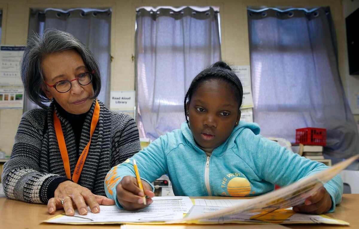 Jalyn Lang, a volunteer at Emerson Elementary School, tutors 4th grader Jordyn Williams in the Reading Partners reading comprehension program in Oakland, Calif. on Thursday, March 14, 2019.