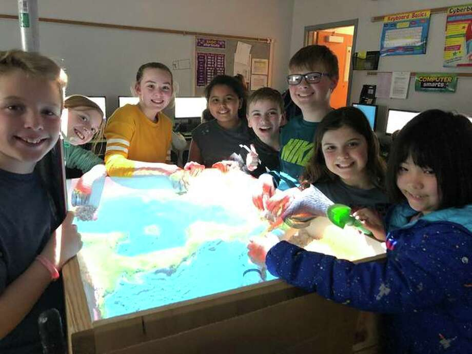 Columbus Elementary School's Tech Club students build the continents of North America and South America using an augmented reality sandbox. Pictured left to right are Jacob Jennings, Serenity Ward, Bella Russo, Sydney Jackson, Sawyer Heck, Brody Sample, Brianna Miller and Madoka Fujinoki. Photo: Julia Biggs | The Intelligencer