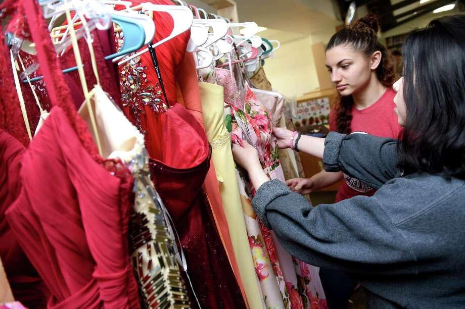 Madison Koval (left), 16 and Shayla Kelly, 17, look through prom dresses at a Prom Shop set up in the library of Derby High School on March 20, 2019. Photo: Arnold Gold / Hearst Connecticut Media / New Haven Register