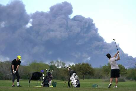 Golfers practice at the Battleground Golf Course driving range as a chemical fire at Intercontinental Terminals Company continues to send dark smoke over Deer Park Tuesday, March 19, 2019. The fire began Sunday morning.