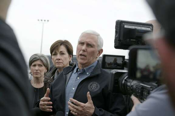 Vice President Mike Pence, center speaks to reporters upon arriving to Omaha, Neb., Tuesday, March 19, 2019, to view the extent of recent flooding and to offer support, with Sen. Joni Ernst, R-Iowa, left, Iowa Gov. Kim Reynolds, second left. (AP Photo/Nati Harnik)