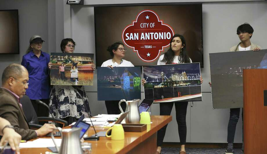 Protesters hold Hays Street Bridge photographs as the San Antonio City Council heads to an executive session during a B-Session March 20. A land swap to settle the dispute over land near the bridge is not enough to satisfy the protesters. Photo: Jerry Lara /Staff Photographer / © 2019 San Antonio Express-News