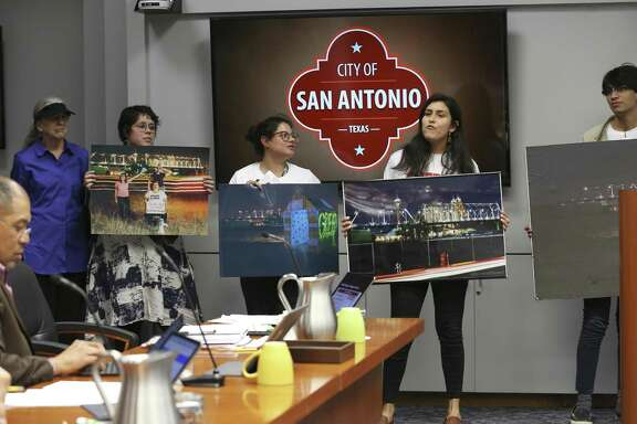 Protesters hold Hays Street Bridge photographs as the San Antonio City Council goes into an executive session to discuss its legal battle over the bridge on March 20, 2019. A community coalition is fighting the city in order to use the land next to the historic Hays Street Bridge as a public park.