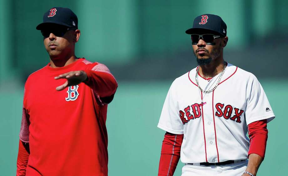 FILE - In this Sept. 16, 2018, file photo, Boston Red Sox manager Alex Cora, left, escorts Mookie Betts off the field during the sixth inning of the team's baseball game against the New York Mets in Boston. Betts drove in just 80 runs last year while spending almost all of his time as the Red Sox leadoff hitter. That seemed like a missed opportunity, so Cora is planning to bat Betts second this season and move Andrew Benintendi to leadoff. (AP Photo/Michael Dwyer, File) Photo: Michael Dwyer / Copyright 2018 The Associated Press. All rights reserved