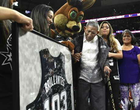 Liban Brillantes, 103, who was born in the Philippines and served in the Army's 121st Infantry Division, is presented with a jersey as he is honored during a timeout of the Miami Heat at San Antonio Spurs NBA game in the AT&T Center on Wednesday, March 20, 2019. Brillantes was only 19 when he served as a messenger between the U.S. and Philippine governments during World War II. He witnessed an execution of prisoners by Japanese soldiers and found one prisoner alive. He carried him into the jungle and nursed him back to health. His granddaughtter, Precious Joy Ross, and daughter, Febelyn Janacek, right, accompany him.