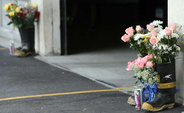 Boots filled with flowers stand outside the Bridgeport Ocean Terrace firehouse on Sunday, July 25, 2010. Two firefighters, Lt. Steven Velasquez and Michel Baik,  died fighting a fire on Elmwood Ave. on Saturday. Photo: B.K. Angeletti / Connecticut Post