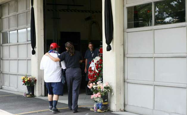 Members of the community offer condolences to the firehouse on Ocean Terrace in Bridgeport after two firefighters, Lt. Steven Velasquez and Michel Baik, died fighting a fire on Saturday. Photo: B.K. Angeletti / Connecticut Post
