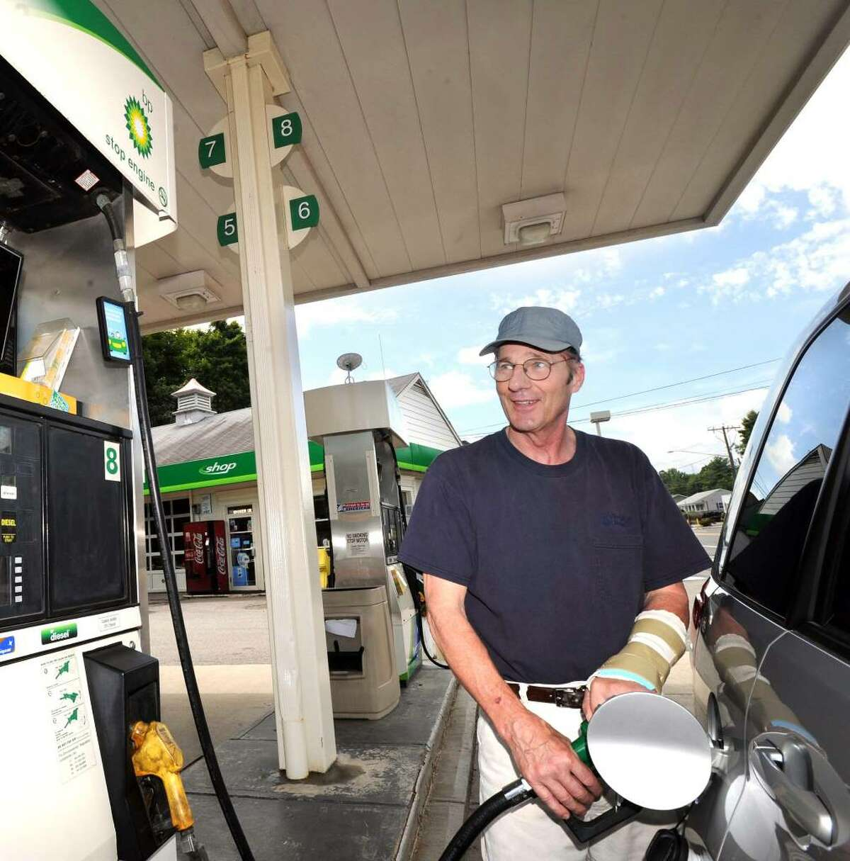 Stephen Sprindis of Brookfield pumps gas at the BP station at the Four Corners in Brookfield Sunday, July 25, 2010.