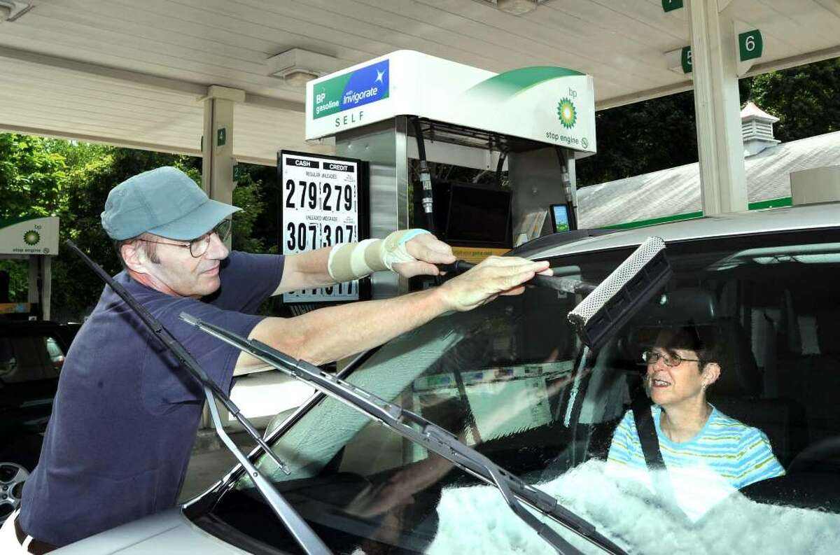 Stephen Sprindis of Brookfield, with Marlana, washes his car windows, while getting gas at the BP station at the Four Corners in Brookfield Sunday, July 25, 2010.