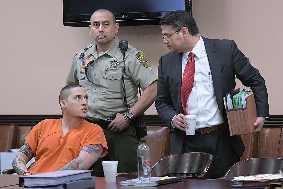 Ronald Anthony Burgos-Avilés, sentado, y su ex abogado defensor Silverio Martínez se miran el uno al otro el miércoles, 20 de marzo de 2019, después de una audiencia para su juicio por dos cargos de homicidio capital, en la 49ava. Corte de Distrito. Photo: Cuate Santos /Laredo Morning Times / Laredo Morning Times