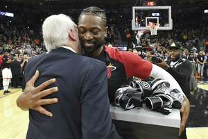 DeWayne Wade, veteran guard of the Miami heat, who is retiring at the end of the season, embraces San Antonio Spurs coach Gregg Popovich after receiving a gift before the teams' NBA game in the AT&T Center on Wednesday, March 20, 2019.