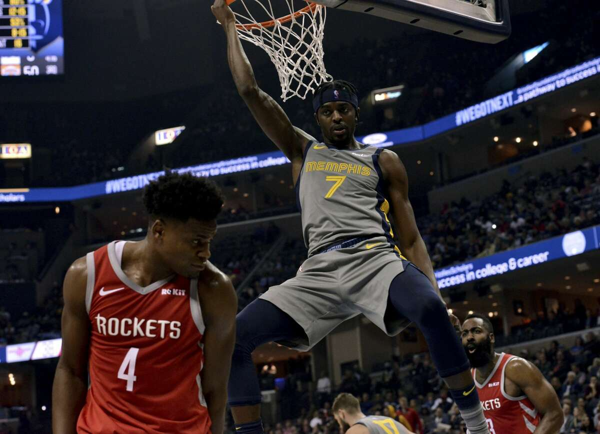 Memphis Grizzlies forward Justin Holiday (7) hangs from the rim after dunking the ball against Houston Rockets forward Danuel House Jr. (4) in the first half of an NBA basketball game Wednesday, March 20, 2019, in Memphis, Tenn. (AP Photo/Brandon Dill)