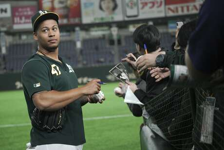 Oakland Athletics pitcher Frankie Montas gives his autograph to fans prior to their pre-season exhibition baseball game against the Nippon Ham Fighters at Tokyo Dome in Tokyo Monday, March 18, 2019. (AP Photo/Eugene Hoshiko)
