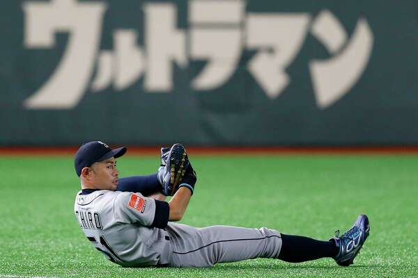 "Seattle Mariners right fielder Ichiro Suzuki stretches on the field prior to Game 2 of the Major League baseball opening series between the Mariners and the Oakland Athletics at Tokyo Dome in Tokyo, Thursday, March 21, 2019. Ichiro is in the starting lineup for the Mariners in what might be his last game in the majors. Japanese in the background reads: ""Ultraman."""