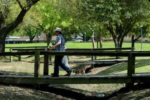 Blake Crandall, 17, and his sister Maddie, 15, walk thsir dog at Dow Park Wednesday, March 20, 2019, in Deer Park, Texas.