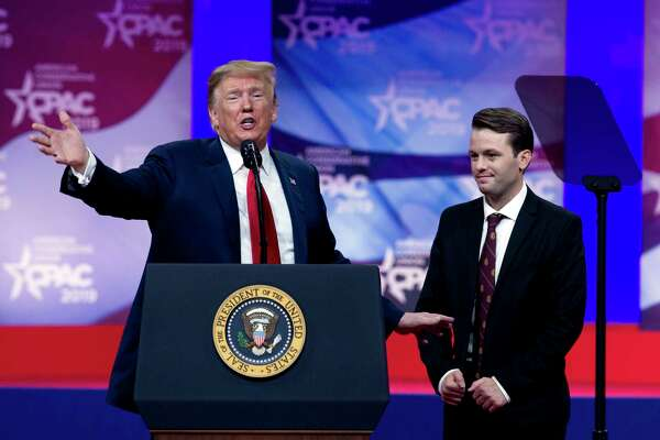 In this March 2, 2019 photo, President Donald Trump invites to the podium, Hayden Williams, a field representative of the Leadership Institute, who was assaulted at Berkeley campus, at the Conservative Political Action Conference, CPAC 2019, in Oxon Hill, Md. Trump is expected to order U.S. colleges to protect free speech on their campuses or risk losing federal funding. White House officials say Trump will sign an executive order Thursday requiring colleges to certify that their policies support free speech as a condition of receiving federal research grants. Trump initially proposed the idea during a March 2 speech to conservative activists.