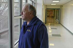 Jim Pacific, an armed school security guard, looks out one of the hallway windows at Reed Intermediate School, in Newtown on Tuesday.