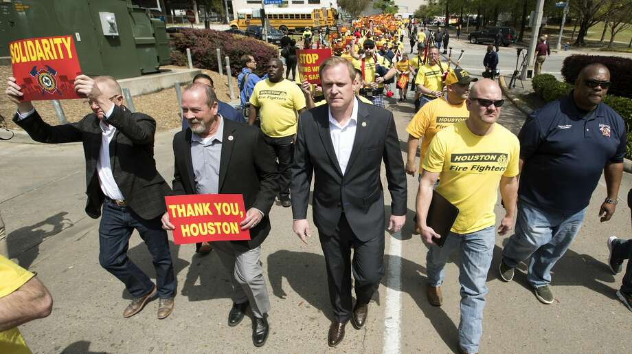 Marty Lancton, center, the head of the Houston Professional Fire Fighters Association, leads a march on City Hall over the labor dispute related to Proposition B on Tuesday, March 19, 2019, in Houston. Mayor Sylvester Turner recently told council members he intends to lay off up to 400 firefighters to fund the pay raises mandated by Prop. B. Photo: Brett Coomer/Staff Photographer