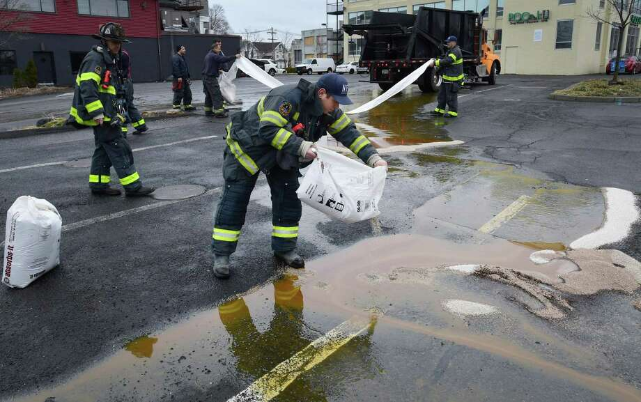 Norwalk emergency personnel respond to the railroad bridge on East Avenue where a cooking oil recycling truck struck the Metro-North bridge rupturing the main tank and spilling over 100 gallons of cooking oil onto the street and parking lot at the East Norwalk Northbound train station on Thursday morning, Below, Photo: Erik Trautmann / Hearst Connecticut Media / Norwalk Hour