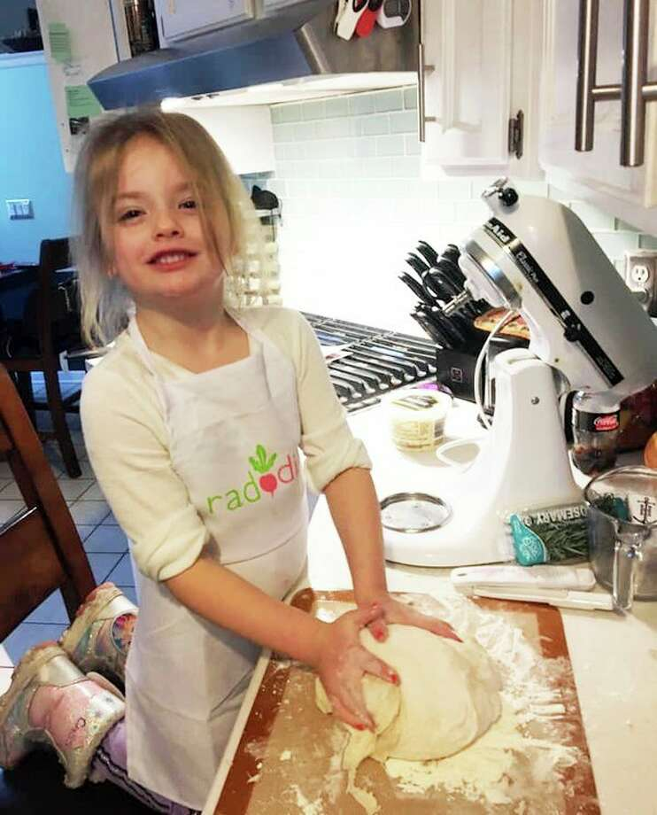 The writer's granddaughter helps in the kitchen. (Photo provided)