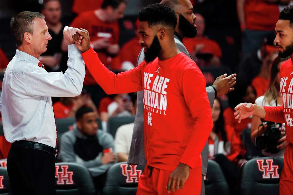 Houston trainer John Houston bumps fists with guard Corey Davis Jr. (5) before an NCAA basketball game against Central Florida at Fertitta Center on Saturday, March 2, 2019, in Houston.