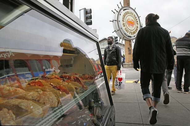 Tourists pass the crab stands along Fisherman's Wharf in San Francisco, California, on Thurs. May 5, 2016.