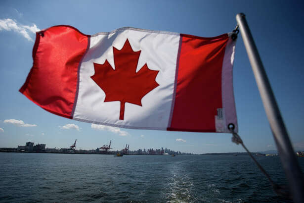 A Canadian flag flies from a Harbour Authority patrol boat as gantry cranes are seen at the Port of Vancouver in Vancouver, British Columbia, on July 11, 2017.