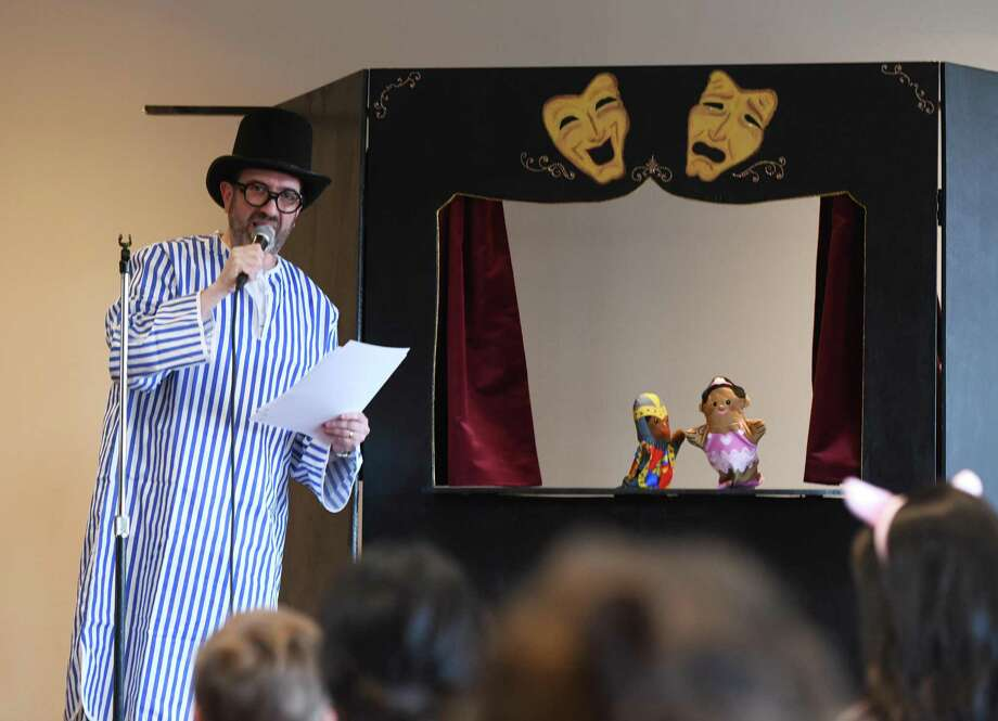 "Nursery School Director David Cohen plays narrator for the Purim puppet show ""Esther Saves the Day"" at Temple Sholom in Greenwich, Conn. Wednesday, March 20, 2019. Children dressed up in costumes and celebrated Purim with a puppet show, baking of hamantaschen, and Megillah reading and shpiel. In the Jewish faith, Purim commemorates the saving of the Jewish people from Haman. Photo: Tyler Sizemore / Hearst Connecticut Media / Greenwich Time"
