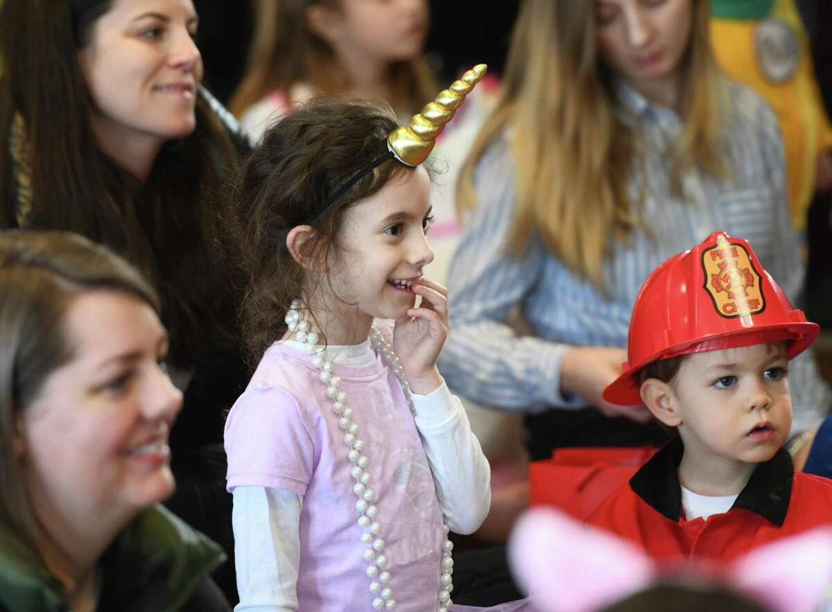 Dressed as a unicorn, Greenwich's Charlie Brahms, 7, enjoys the Purim puppet show